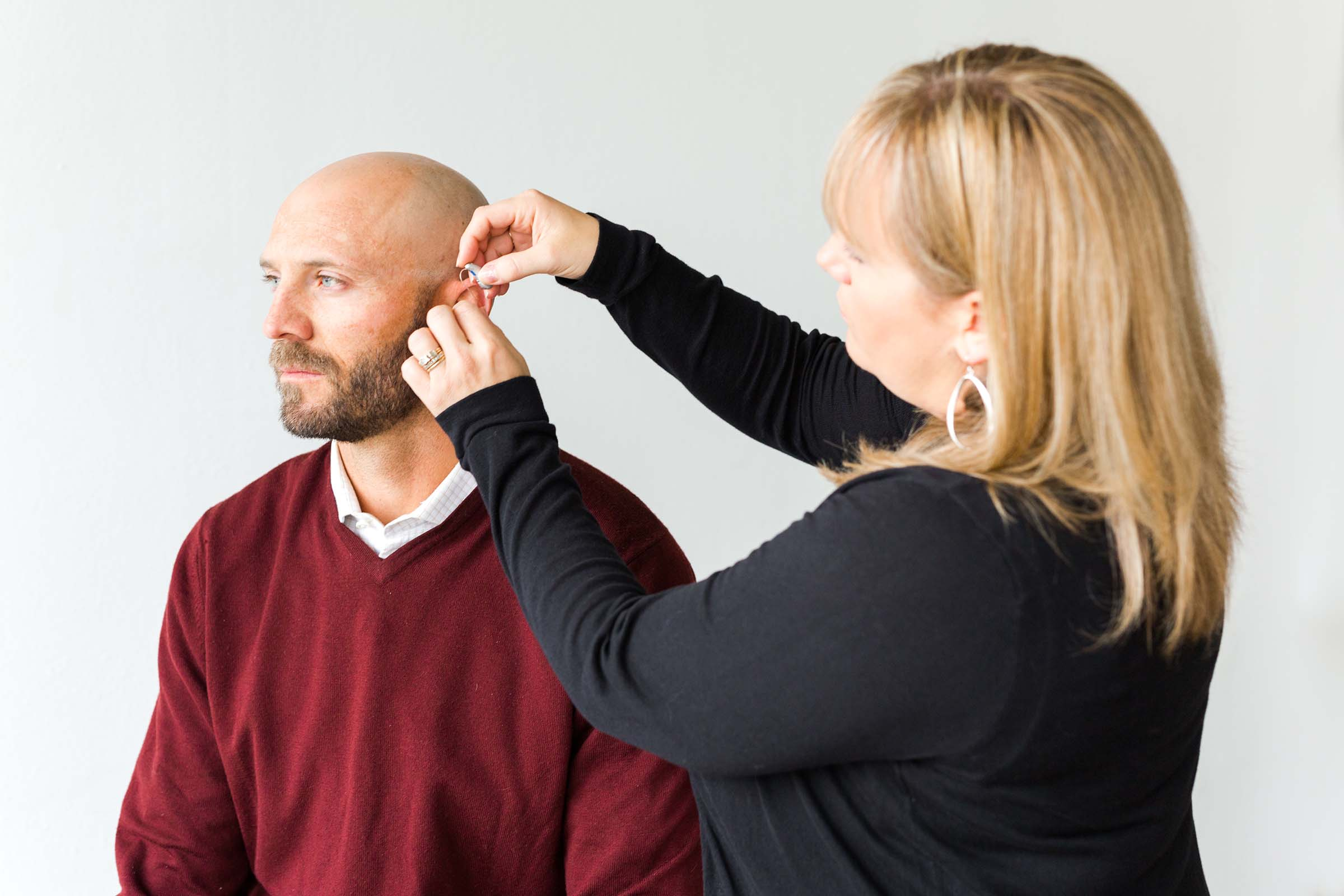 Woman fitting man with hearing aid